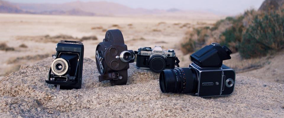 A variety of vintage film cameras sitting on a rock in the desert