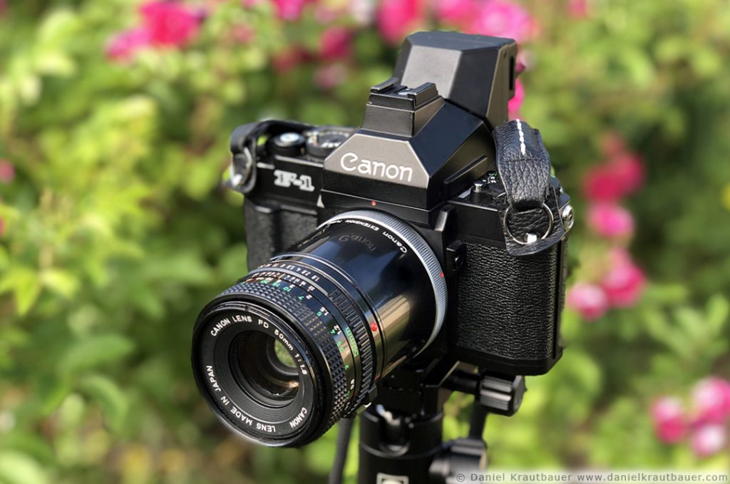 A Canon F1 SLR camera with a 50mm extension tube and 50mm lens attached