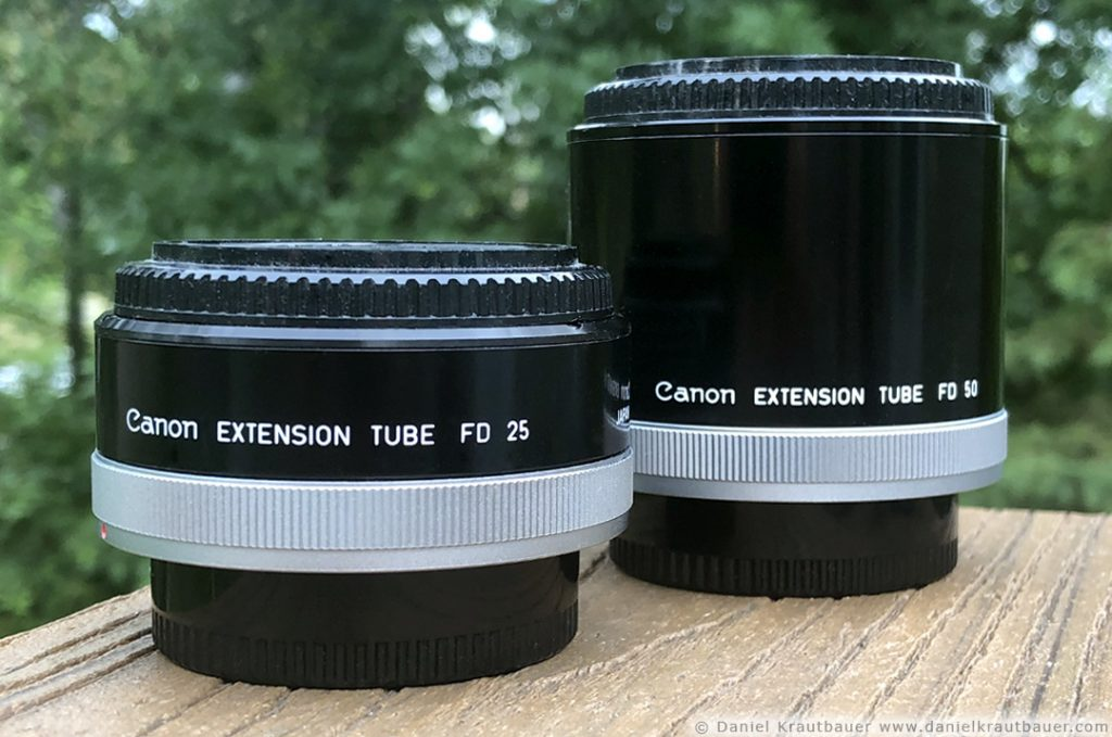 Photo of two extension tubes (round, black cylinders) for Canon SLR cameras